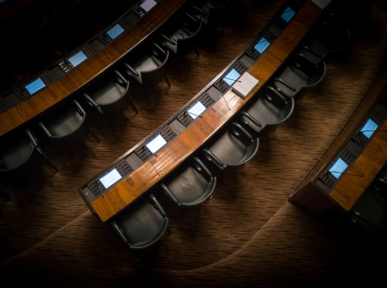 low light photography of armchairs in front of desk